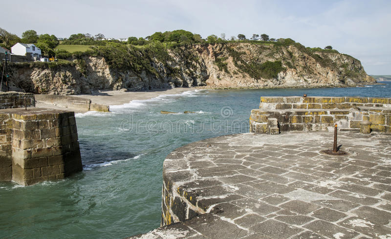 Harbour entrance and beach at Charlestown, Cornwall. With cliffs and countryside in background stock photo