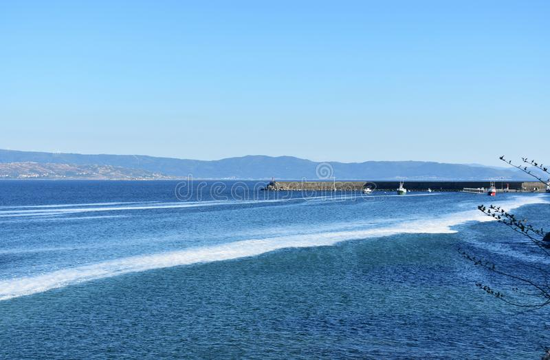Harbour with fishing boats in a bay. Blue sea with foam, clear sky, sunny day. Galicia, Spain. stock photos