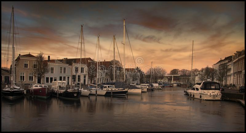 Harbour of Goes, The Netherlands. Photo was taken during winter. The harbor is frozen, so the late afternoon sky is reflected beautiful in the frozen water stock photos