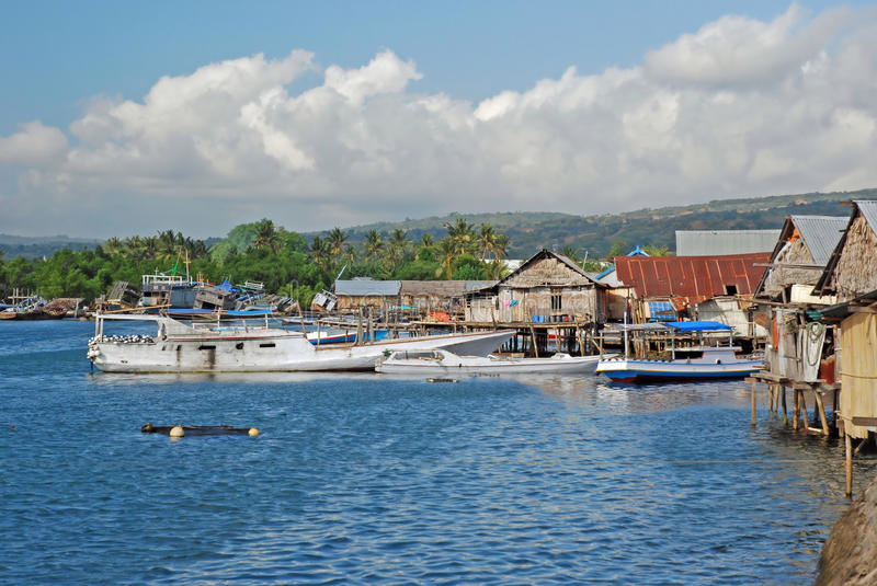Harbour and houses on stilts, Maumere, Indonesia. Harbour with Residential houses on stilts of bamboo/wood with metal golf roofs, Maumere, Flores, Lesser Sunda royalty free stock photo