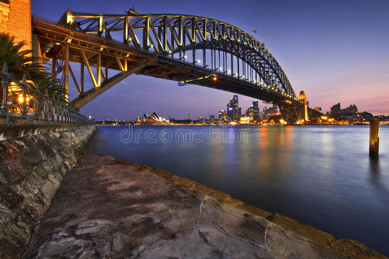 Harbour Nights. Sunset over the harbour at Sydney Harbour - looking under the Sydney Harbour Bridge to the Sydney Opera House, Australia royalty free stock images