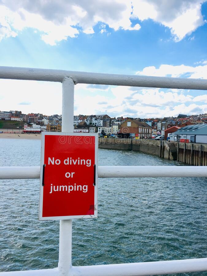 Scarborough, North Yorkshire, United Kingdom. The harbour and no diving sign at Scarborough, North Yorkshire, United Kingdom stock images