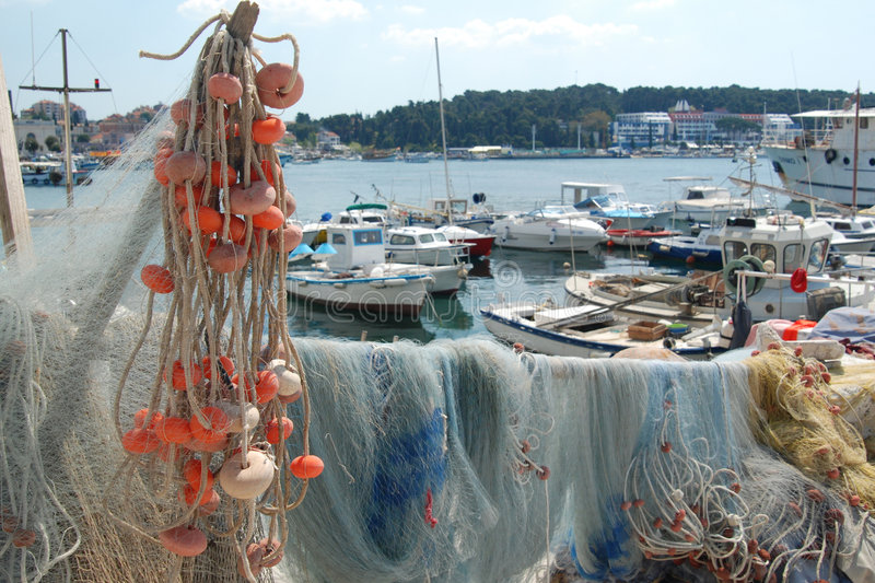Harbour in Rovigno. Fishermans net drying up under the sun in a harbour with boats - Rovigno, Croazia stock photo