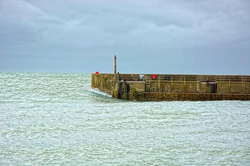 Harbour wall and heavy sea swell. A heavy sea swell approaches a harbour wall as fisherman attempt to make a catch from the structure under a stormy sky stock photo