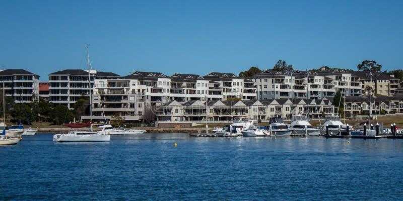 Harbourside-Kondominium-Wohnungswohnung mit den Booten, die auf blaues Wasser gegen blauen Himmel schwimmen stockfoto