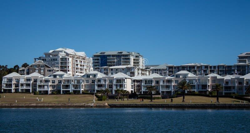 Harbourside-Kondominium-Wohnungswohnung mit Grasfront gegen blaues Wasser und Himmel stockfoto