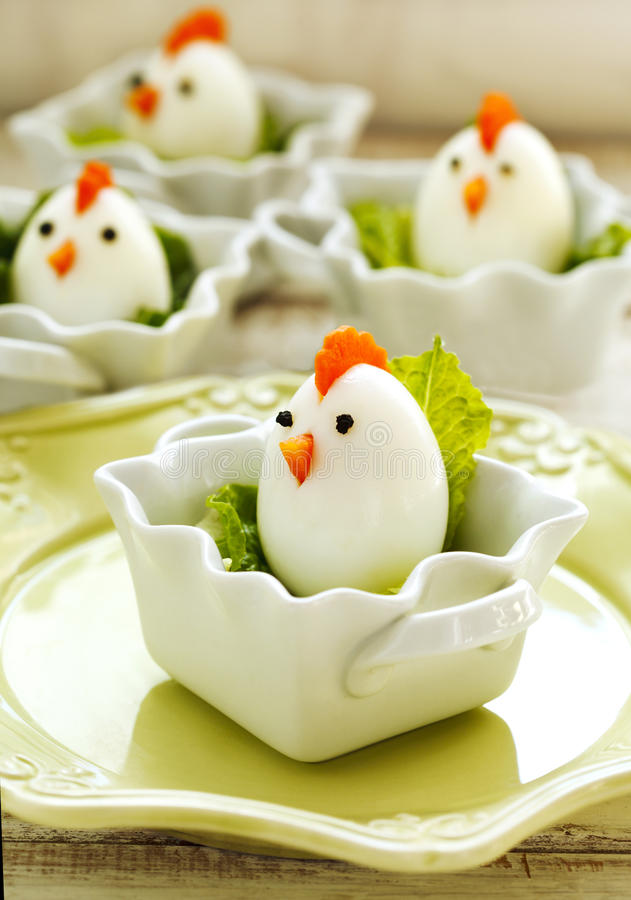 Hard boiled Chicken Egg Family. Easter food for kids. Hard boiled Chicken Egg Family served with lettuce. Easter food for kids royalty free stock photo