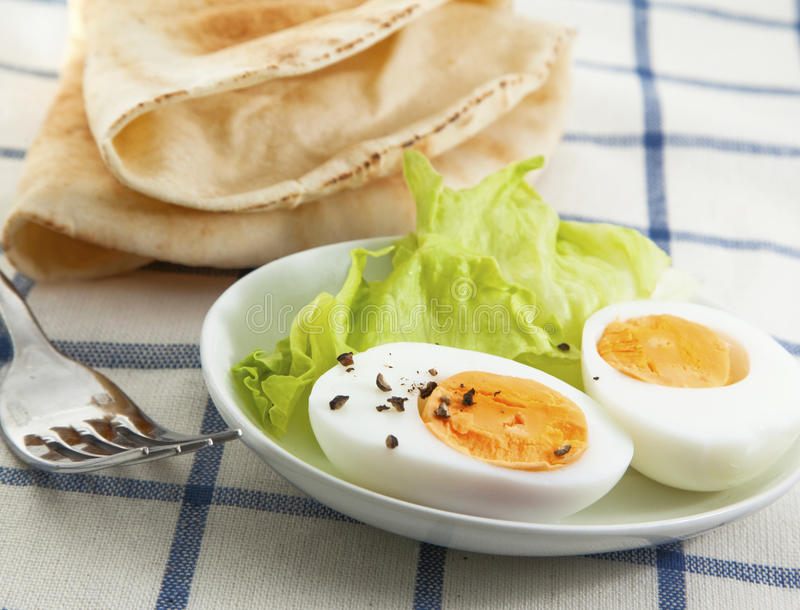 Hard boiled egg. With salad on the textile background stock image
