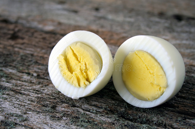 Hard Boiled Egg. A hard boiled egg sliced in two ready to be eaten royalty free stock images