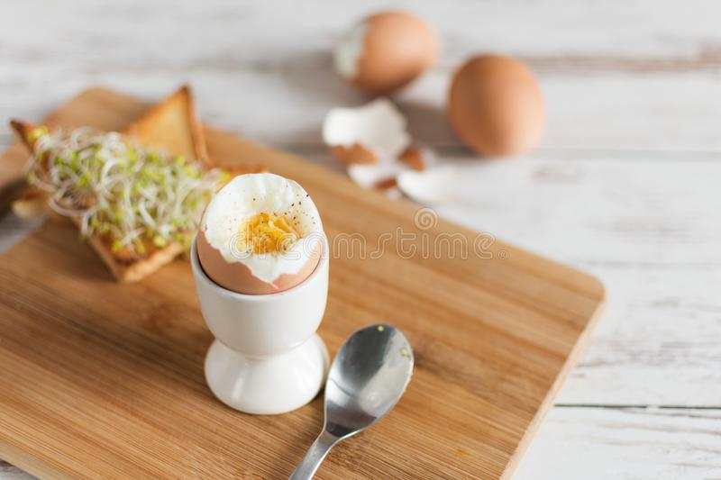 Hard boiled egg and bread sandwich with sprouted grain on a wooden table. Traditional food for healthy breakfast stock photos