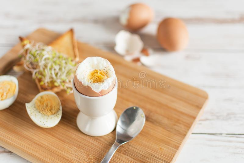 Hard boiled egg and bread sandwich with sprouted grain on a wooden table. Traditional food for healthy breakfast royalty free stock images