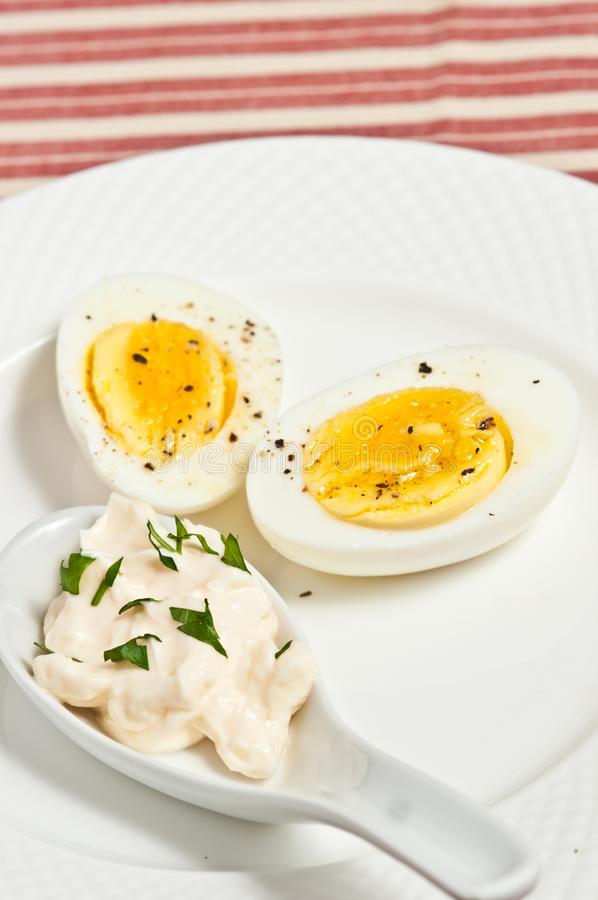 Hard boiled egg and ceramic spoon of mayo with parsley. Top view, close distance of a halved hard boiled egg with firm yolk with cracked, black pepper and a stock photography