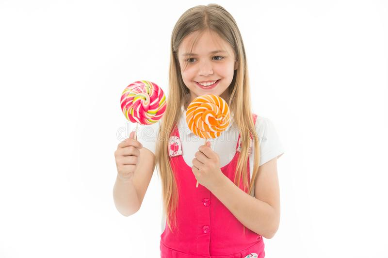 Hard choice. Cheerful little girl holding lollipops in her hands and smiling while standing isolated on white. Girl can royalty free stock photo