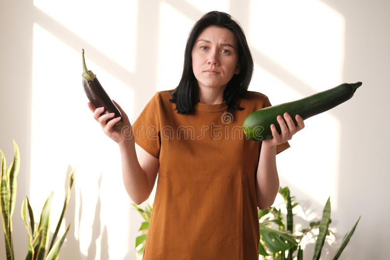 The girl in a T-shirt does not know what to choose - eggplant or zucchini. Hard choice. stock images