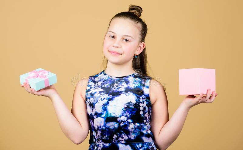 Hard choice. Surprise. Childrens day. Congratulation. Small girl with present box. Happy birthday. Holiday celebration. Cheerful child. Little girl with gift royalty free stock image