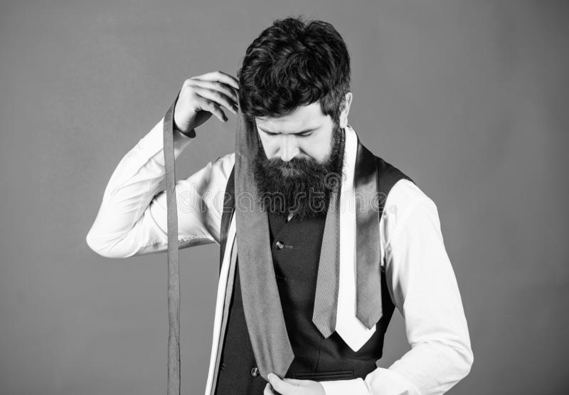 Hard choice to make. Bearded man choosing tie from luxury collection, choice concept. Salesman offering a good choice of. Design neckties. Brutal hipster making royalty free stock photography