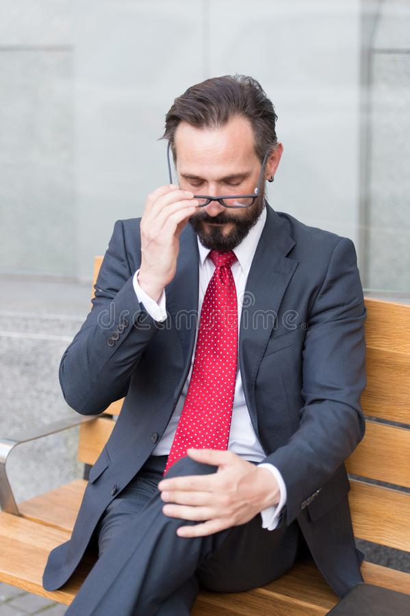 Tired banker fixing his glasses while sitting on bench and looking down. Hard day. Exhausted bearded banker sitting outdoors and crossing his legs while fixing royalty free stock images