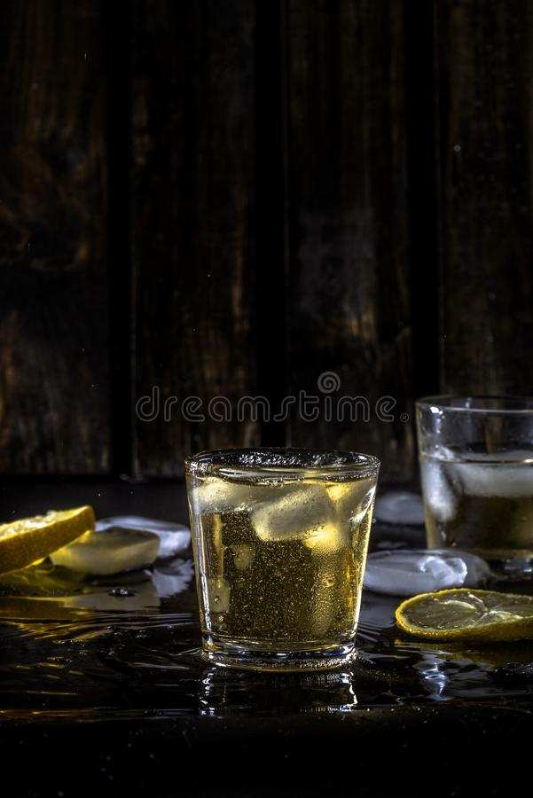 A hard day`s night. Whisky in the bar, alcohol with ice cubes. drunk man, good rest. quiet company, happiness, love, hope. sparks of the night city, people royalty free stock photography