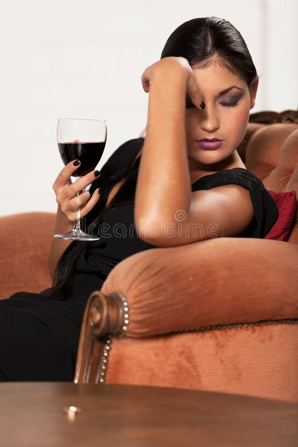 Hard decision to make. Girl with red wine is taking hard decision royalty free stock images