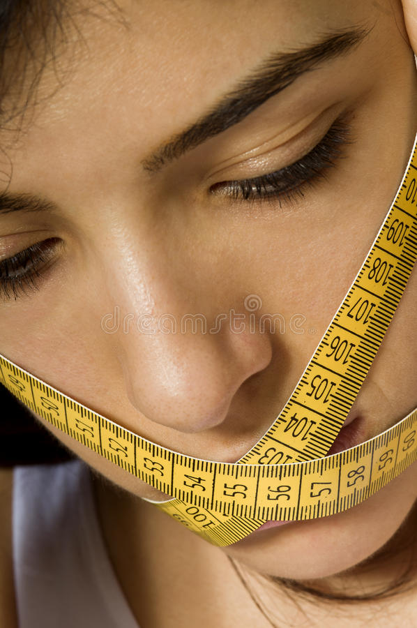 Eating Disorder. Photo of a beautiful young girl. She is in trouble because of forbidden eating disorders with hard dietary rules. Her mouth is crossed and her stock images