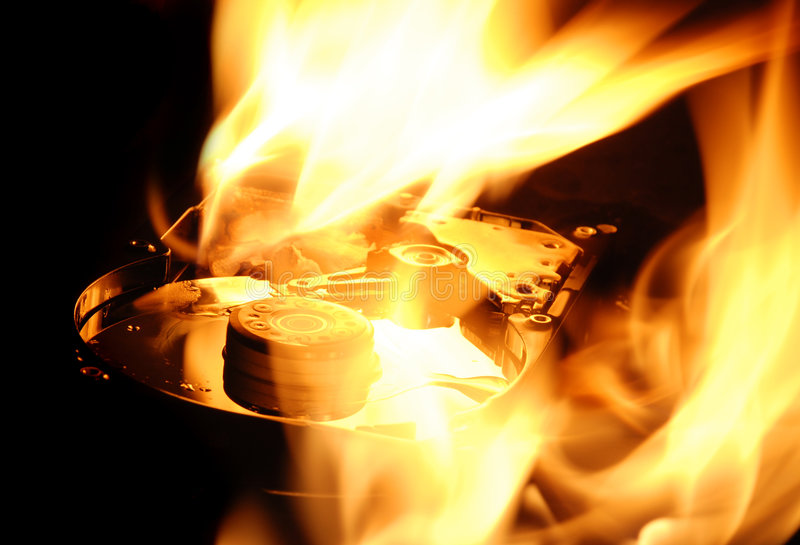 Hard disk on fire. Internal mechanics of a hard disc drive on fire emphasising data security importance stock photo
