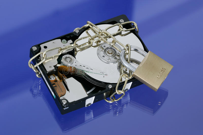 Hard disk with padlock and chain. Opened hard disk secured with an iron chain and padlock on blue background royalty free stock photo