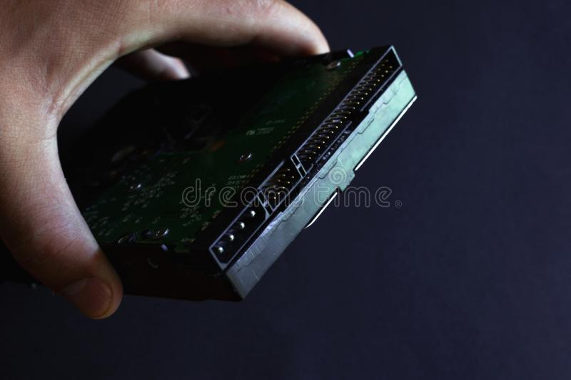 Hard drive in hand, solid state hdd drive on a dark background. Closeup royalty free stock photo