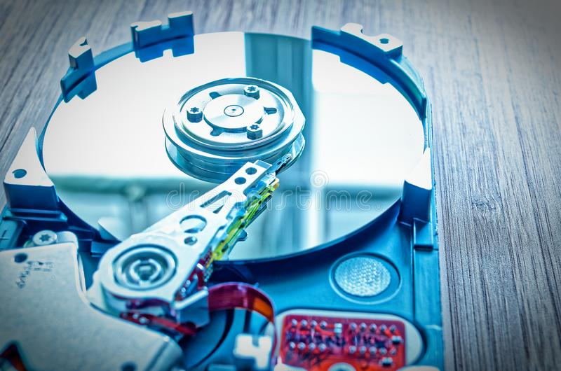 Hard drive 3.5 inches as a data storage with motherboard on a bamboo table. In blue design royalty free stock photography