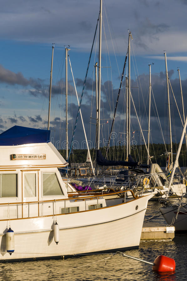 Hard evening light harbour. Hard evening light on moored leisure boats in Mariefred guest harbour. Södermanland, Sweden royalty free stock image