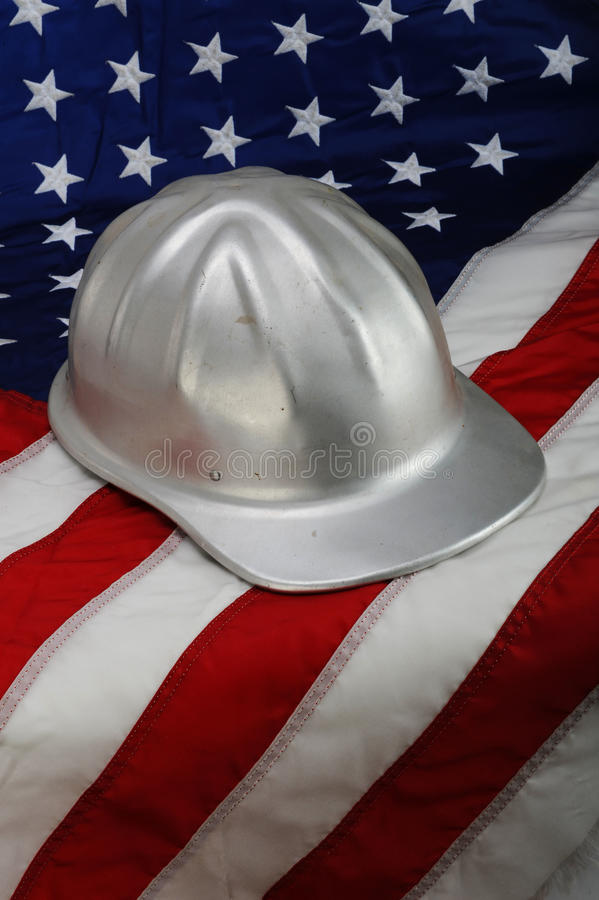 Hard Hat on American Flag. America back to work. Construction hard hat laying on an American flag - metaphor for increased employment, more jobs royalty free stock images