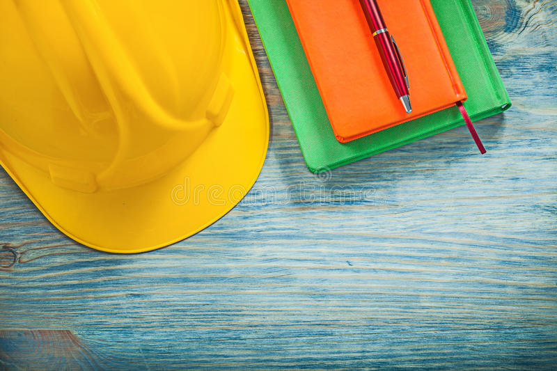 Hard hat notepads ball-point pen on wooden board construction co. Ncept stock photo