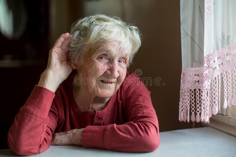 Hard-of-hearing elderly woman stock image