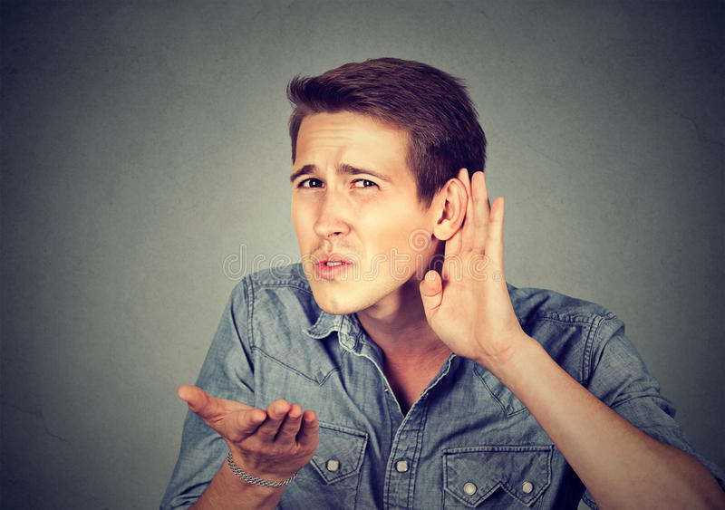 Hard of hearing man placing hand on ear asking someone to speak up stock photo