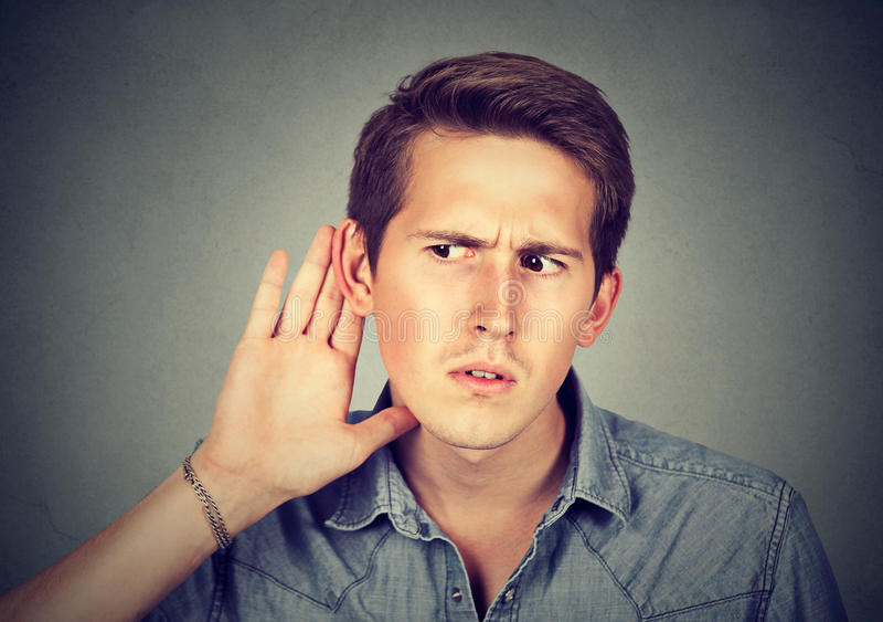 Hard of hearing man placing hand on ear listening to gossip. Closeup portrait hard of hearing man placing hand on ear asking someone to speak up or listening stock photography