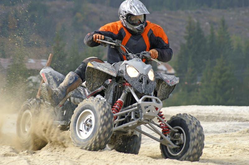 Hard left turn. Aggressive looking sport ATV splashing sand royalty free stock photos
