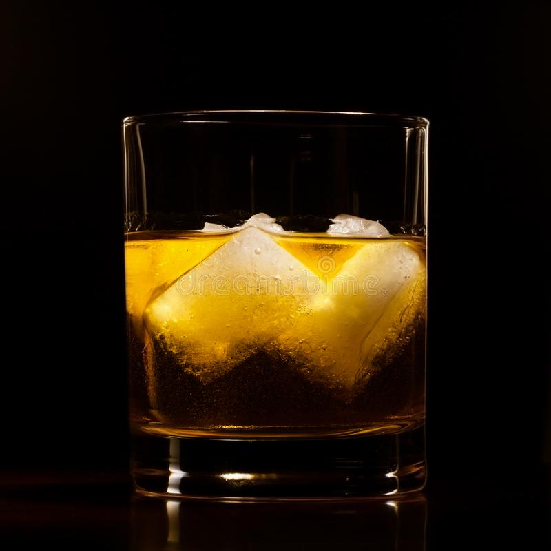 Hard liquor on rocks. Amber volor hard liquor on rocks on black royalty free stock image