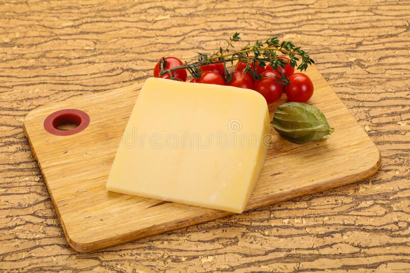 Hard parmesan cheese piece. Over wooden background stock photos