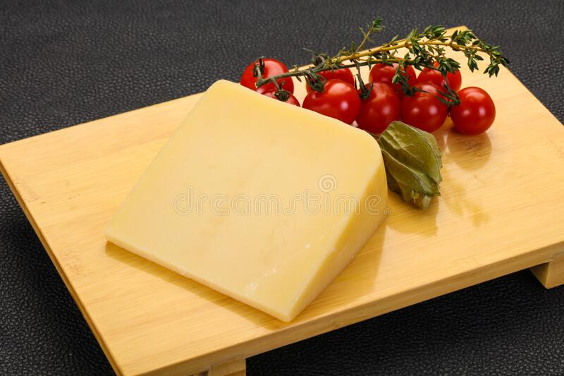 Hard parmesan cheese piece. Over wooden background royalty free stock photos