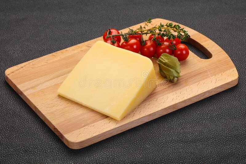 Hard parmesan cheese piece. Over wooden background stock image