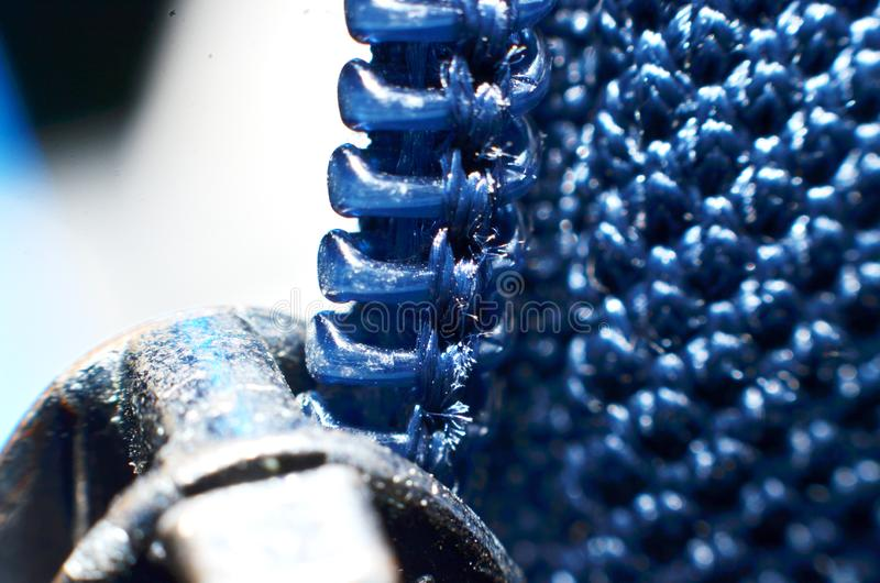 Hard plastic jacket zippers, shaped like teeth. Arranged in long lines down in blue royalty free stock photos