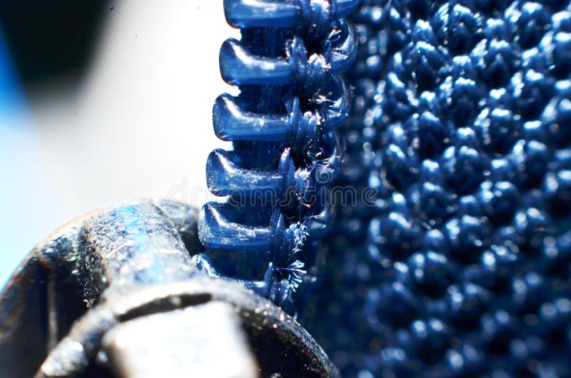 Hard plastic jacket zippers, shaped like teeth. Arranged in long lines down in blue royalty free stock images