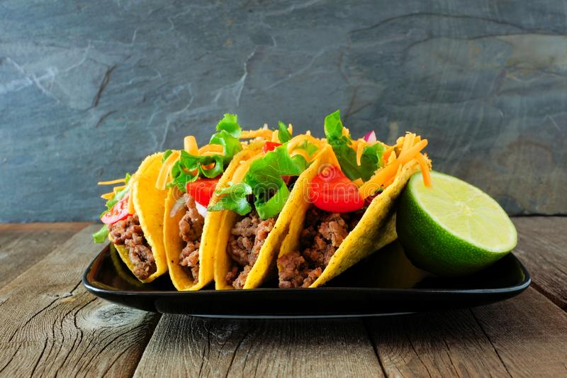 Hard shelled tacos with ground beef, vegetables and cheese on a dark background stock images