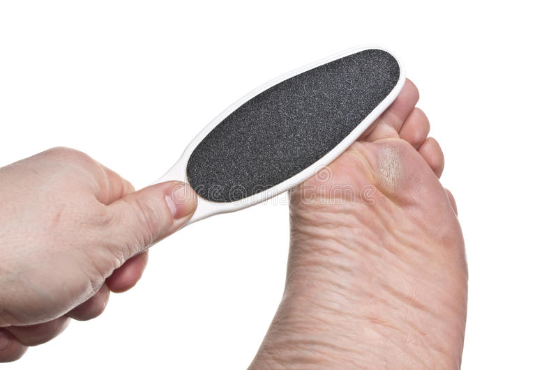 Hard skin removal. On one man's foot royalty free stock photography