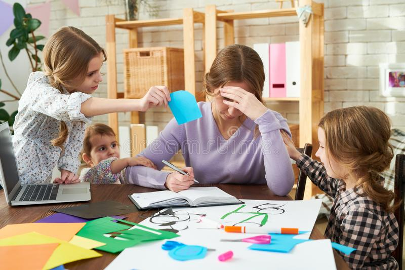 Hard Time of Freelance Worker. Exhausted freelance worker trying to concentrate on project while her little daughters distracting her, interior of modern living stock image