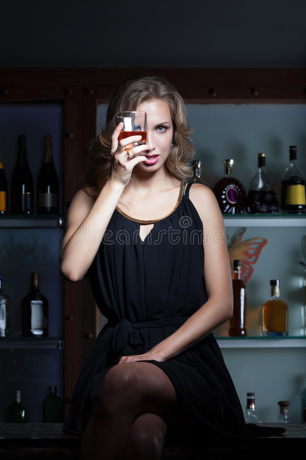 Hard times in the bar. Woman with the glass of whiskey sitting on the bar counter royalty free stock photos