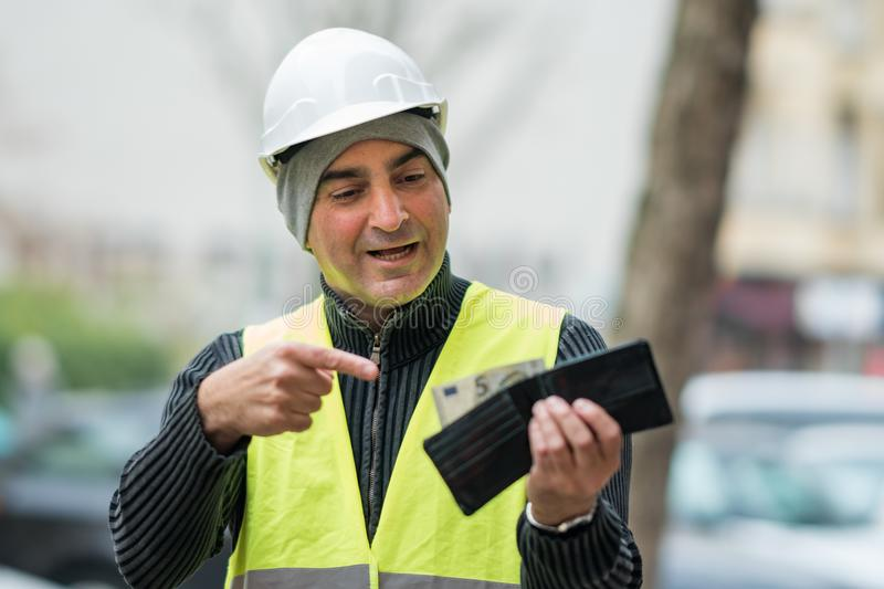 Bad times: poor construction worker and his empty wallet. Hard times: poor construction worker and his empty wallet. Outdoors stock photos