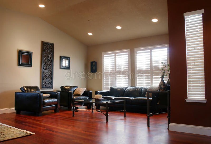 Hard Wood Living. Modern Living Room with Table and Chairs with Hardwood Cherry Floor and Black Leather Sofas