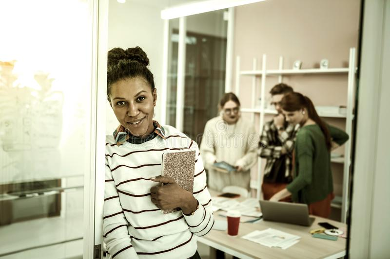 Hard-working African-American student standing with cute notebook. Student with notebook. Hard-working African-American student standing with her cute bright stock photo