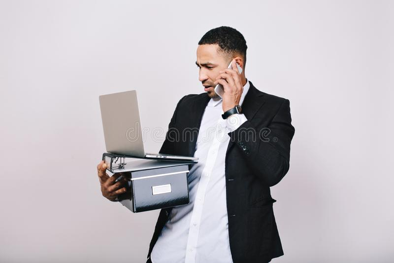 Hard-working astonished businessman with office box, folders, laptop talking on phone on white background. Office worker. Career, smart manager royalty free stock image