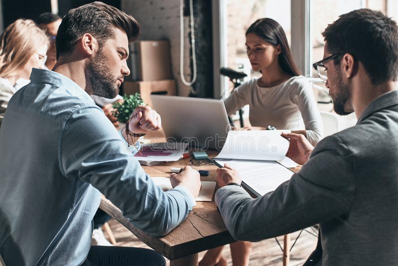 Hard working day. Young modern people in smart casual wear working together while sitting in the creative office royalty free stock photos